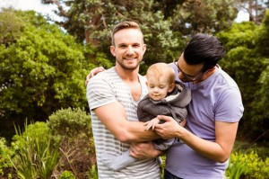 52102075 - smiling gay couple with child in garden