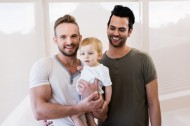 52102476 - smiling gay couple with child at home